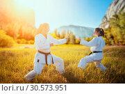 Купить «Two female karate in kimono training combat skill», фото № 30573951, снято 26 августа 2018 г. (c) Tryapitsyn Sergiy / Фотобанк Лори