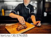 Купить «Сook sprinkle fresh prepared steak with seasoning», фото № 30574055, снято 27 августа 2018 г. (c) Tryapitsyn Sergiy / Фотобанк Лори