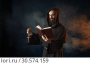 Medieval monk praying with book in church. Стоковое фото, фотограф Tryapitsyn Sergiy / Фотобанк Лори