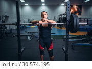 Купить «Muscular athlete poses at the stand with barbell», фото № 30574195, снято 4 сентября 2018 г. (c) Tryapitsyn Sergiy / Фотобанк Лори