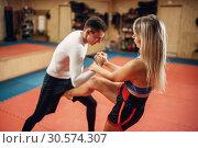 Купить «Female fighter hiding from a knife strike», фото № 30574307, снято 9 сентября 2018 г. (c) Tryapitsyn Sergiy / Фотобанк Лори