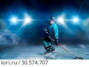 Купить «One hockey player on ice, spotlights on background», фото № 30574707, снято 20 апреля 2017 г. (c) Tryapitsyn Sergiy / Фотобанк Лори