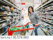 Купить «Young woman with cart full of goods in supermarket», фото № 30574983, снято 28 октября 2018 г. (c) Tryapitsyn Sergiy / Фотобанк Лори