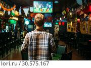 Купить «Football fan watching the match in sports bar», фото № 30575167, снято 30 октября 2018 г. (c) Tryapitsyn Sergiy / Фотобанк Лори