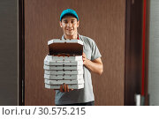 Купить «Delivery man shows fresh pizza, delivering service», фото № 30575215, снято 4 ноября 2018 г. (c) Tryapitsyn Sergiy / Фотобанк Лори
