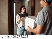 Купить «Customer takes order from pizza delivery boy», фото № 30575235, снято 4 ноября 2018 г. (c) Tryapitsyn Sergiy / Фотобанк Лори