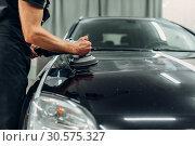 Male person with polishing machine cleans car. Стоковое фото, фотограф Tryapitsyn Sergiy / Фотобанк Лори