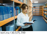 Купить «Female student reading book at bookshelf, library», фото № 30575799, снято 5 декабря 2018 г. (c) Tryapitsyn Sergiy / Фотобанк Лори
