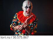 Купить «Bloody clown holds human hand, finger in his teeth», фото № 30575867, снято 7 декабря 2018 г. (c) Tryapitsyn Sergiy / Фотобанк Лори