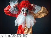 Scary bloody clown tears his hair, jerk in anger. Стоковое фото, фотограф Tryapitsyn Sergiy / Фотобанк Лори