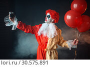 Scary bloody clown with crazy eyes makes selfie. Стоковое фото, фотограф Tryapitsyn Sergiy / Фотобанк Лори