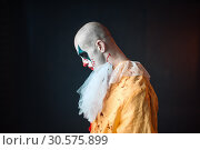 Sad bloody clown with makeup in carnival costume. Стоковое фото, фотограф Tryapitsyn Sergiy / Фотобанк Лори