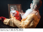 Купить «Bloody clown with crazy eyes sitting at the mirror», фото № 30575903, снято 7 декабря 2018 г. (c) Tryapitsyn Sergiy / Фотобанк Лори
