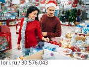 Купить «Young couple chooses christmas tree toys in shop», фото № 30576043, снято 13 декабря 2018 г. (c) Tryapitsyn Sergiy / Фотобанк Лори