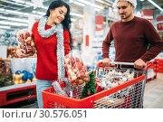 Купить «Young couple put in a cart Christmas decorations», фото № 30576051, снято 13 декабря 2018 г. (c) Tryapitsyn Sergiy / Фотобанк Лори