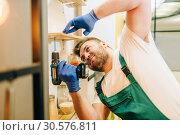 Repairman in uniform holds screwdriver, handyman. Стоковое фото, фотограф Tryapitsyn Sergiy / Фотобанк Лори