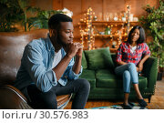Купить «Black man sitting in a chair against his woman», фото № 30576983, снято 5 марта 2019 г. (c) Tryapitsyn Sergiy / Фотобанк Лори