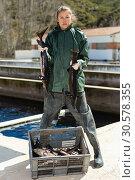 Купить «Woman holding sturgeon», фото № 30578355, снято 19 марта 2019 г. (c) Яков Филимонов / Фотобанк Лори