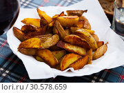 Купить «Delicious baked in oven yellow potatoes served at plate», фото № 30578659, снято 21 апреля 2019 г. (c) Яков Филимонов / Фотобанк Лори