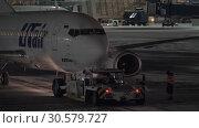 Купить «Utair airplane pushback. Night view at Vnukovo Airport in Moscow, Russia», видеоролик № 30579727, снято 25 декабря 2017 г. (c) Данил Руденко / Фотобанк Лори