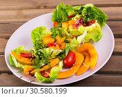 Купить «Salad of baked pumpkin, cherry tomatoes, sesame, sauce and greens», фото № 30580199, снято 15 июня 2019 г. (c) Яков Филимонов / Фотобанк Лори
