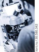 Купить «Scientist microscoping on fluorescent microscope.», фото № 30580343, снято 23 октября 2019 г. (c) Matej Kastelic / Фотобанк Лори