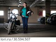 Портрет беременной женщины, стоящей рядом с мотоциклом с белым шлемом в руке, подземный гараж. Стоковое фото, фотограф Кекяляйнен Андрей / Фотобанк Лори
