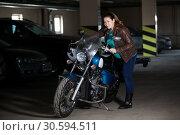Купить «Full-figured woman getting on bike in dark garage, concept of pregnant with motorcycle», фото № 30594511, снято 24 февраля 2019 г. (c) Кекяляйнен Андрей / Фотобанк Лори