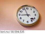 Круглые часы висят на розовой стене. Без пяти девять. Стоковое фото, фотограф Кекяляйнен Андрей / Фотобанк Лори