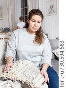 Купить «Уставшая женщина сидит на диване в домашней обстановке, вечером. Ребенок на кухне», фото № 30594583, снято 17 февраля 2019 г. (c) Кекяляйнен Андрей / Фотобанк Лори