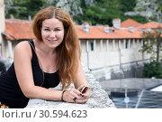 Купить «Счастливая привлекательная женщина на фоне стен древней крепости», фото № 30594623, снято 2 июня 2016 г. (c) Кекяляйнен Андрей / Фотобанк Лори