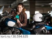 Портрет женщины мотоциклистки, стоящей у мотоцикла в темном гараже. Белый шлем на сиденье. Стоковое фото, фотограф Кекяляйнен Андрей / Фотобанк Лори