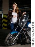 Купить «Беременная женщина, одетая в коричневую кожаную куртку, стоит рядом с мотоциклом, держит руль и свой большой живот», фото № 30594643, снято 24 февраля 2019 г. (c) Кекяляйнен Андрей / Фотобанк Лори