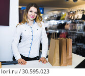Купить «Happy female seller showing numerous purchases», фото № 30595023, снято 20 марта 2017 г. (c) Яков Филимонов / Фотобанк Лори