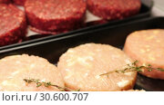 Купить «Fresh beef and chicken cutlets for barbecue are lying in black trays on the store shelf of meat section in slow mo camera motion 4K video with no people», видеоролик № 30600707, снято 5 ноября 2018 г. (c) Uladzimir Sitkouski / Фотобанк Лори