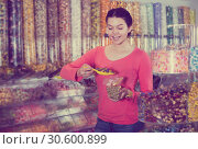Купить «Shopgirl in store is picking up candies», фото № 30600899, снято 22 марта 2017 г. (c) Яков Филимонов / Фотобанк Лори