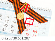 Купить «9 May card - jubilee medal of Great patriotic war and St George ribbon lying on the calendar with framed 9 May date», фото № 30601287, снято 8 апреля 2017 г. (c) Зезелина Марина / Фотобанк Лори