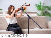 Купить «Female beautiful musician playing violin at home», фото № 30602119, снято 1 октября 2018 г. (c) Elnur / Фотобанк Лори