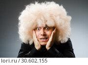 Купить «Young man wearing afro wig», фото № 30602155, снято 15 июня 2014 г. (c) Elnur / Фотобанк Лори