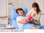 Купить «Loving wife looking after injured husband in hospital», фото № 30603415, снято 24 сентября 2018 г. (c) Elnur / Фотобанк Лори
