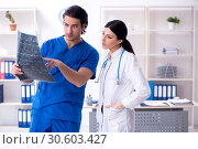 Купить «Two young doctors working in the clinic», фото № 30603427, снято 25 января 2019 г. (c) Elnur / Фотобанк Лори