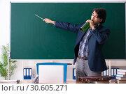 Купить «Male teacher drinking in the classroom», фото № 30605271, снято 21 декабря 2018 г. (c) Elnur / Фотобанк Лори