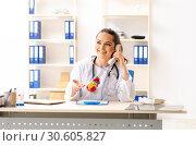Купить «Young female doctor cardiologist sitting at the hospital», фото № 30605827, снято 5 ноября 2018 г. (c) Elnur / Фотобанк Лори