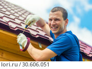 Купить «Happy man is repairing the roof of the house, a portrait on the background of tiles», фото № 30606051, снято 23 июня 2016 г. (c) Константин Лабунский / Фотобанк Лори