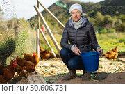 Купить «Young woman farmer caring for poultry», фото № 30606731, снято 18 марта 2019 г. (c) Яков Филимонов / Фотобанк Лори