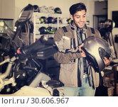 Купить «Man in moto jacket is choosing new helmet for motorbike in the store.», фото № 30606967, снято 1 сентября 2017 г. (c) Яков Филимонов / Фотобанк Лори