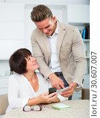 Купить «Son telling mother how to use phone», фото № 30607007, снято 8 июля 2020 г. (c) Яков Филимонов / Фотобанк Лори