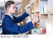 Купить «Young guy joiner searching for items in storage», фото № 30607055, снято 7 ноября 2016 г. (c) Яков Филимонов / Фотобанк Лори