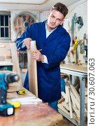 Купить «Man measuring boards for furniture at workshop», фото № 30607063, снято 7 ноября 2016 г. (c) Яков Филимонов / Фотобанк Лори