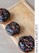 Купить «On the table fresh cupcakes drenched with chocolate and decorative sprinkles diagonally on a wooden Board», фото № 30607511, снято 6 апреля 2019 г. (c) Катерина Белякина / Фотобанк Лори